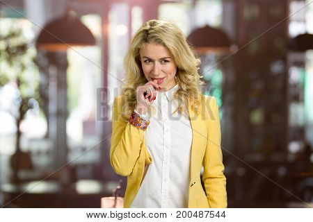 Beautiful woman thinking on blurred background. Attractive young girl in formal wear looking thoughtful on unfocused background.