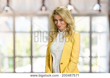 Beautiful shy girl looking at camera. Beautiful embarrassed blonde woman in formal wear posing on blurred background.