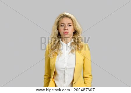 Portrait of bored thoughtful young woman. Tired woman in formal wear looking thinking and worried on grey background.