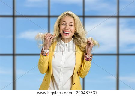 Portrait of happy smiling young woman. Cheerful blond young executive holding her hair and laughing on blue sky office window background.