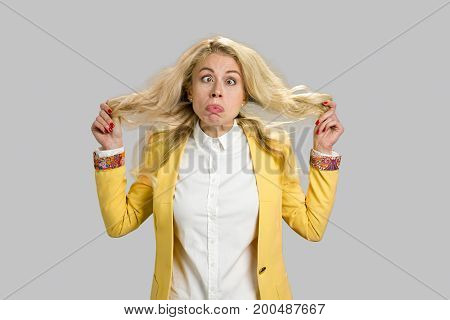 Young woman making grimace. Blond young girl making funny face standing on grey background.