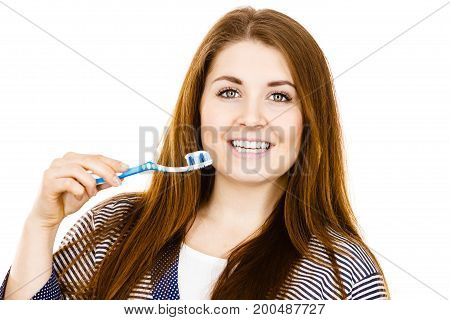 Woman wearing dressing gown holding toothbrush with paste on it. Smiling positive girl ready to cleaning teeth. Oral hygiene. Isolated on white