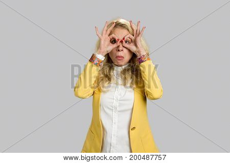 European woman making binoculars with hands. Young serious woman having fun and making binoculars using her hands isolated on gray background.