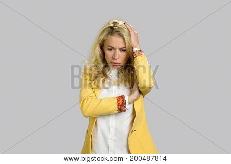 Thoughtful worried young blonde woman. Stressed and worried young blonde woman holding hand on head, grey background.