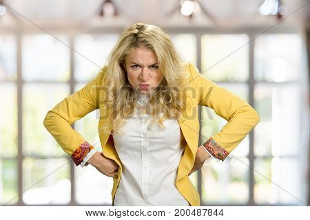 Aggressive frowning young blonde woman. Frustrated european woman in formal wear holding hands on hips with negative emotions, blurred background.
