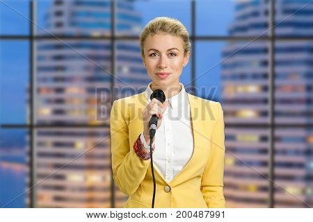 Beautiful lady holding microphone. Waist up portrait of elegant woman reporter standing on office evening background and smiling at camera.