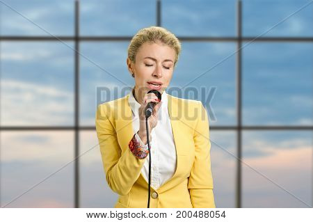 Young lady with microphone closed eyes. Beautiful blonde business woman speaking into microphone on office window background.