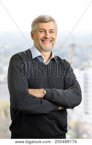 Cheerful mature man crossed arms. Elderly office worker standing with crossed arms and smiling on blurred background.