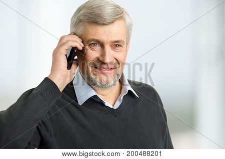 Smiling mature man with phone. Portrait of grey hair man holding phone near ear close up.