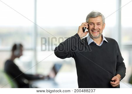 Mature man on office background. Happy man with grey hair talking on phone on office background. Smiling senior man with mobile phone. Facial expressions mature man of good news.