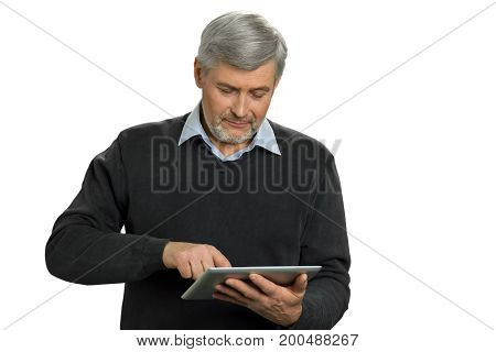 Mature man surfing net on computer tablet. Man with grey hair examining his new computer tablet on white background.