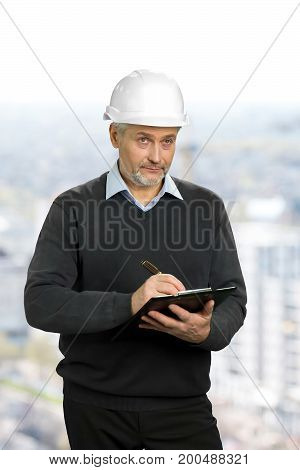Mature architect looking on object. Elderly engineer in safety helmet holding clipboard and checking the object, blurred background.