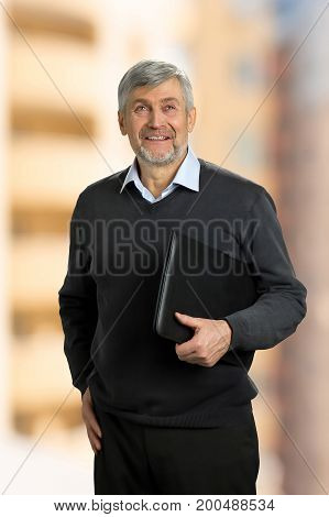 Smiling mature man holding folder. Senior man standing with folder and smiling on blurred background.