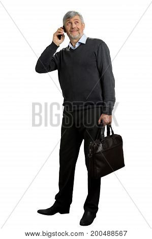 Mature man speaking on phone. Grey hair man with phone looking upwards on white background. Full length portrait.