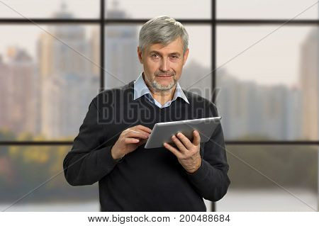Portrait of mature man with pc tablet. Serious grey hair man holding computer tablet on office window background close up. Senior man with digital tablet on blurred background.