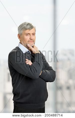 Thoughtful mature man on blurred background. Senior man hold chin on hand and thinking. Lost in thoughts.