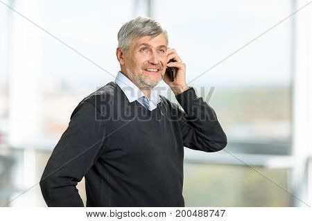 Portrait of mature man with phone. Smiling senior man with phone smiling and looking upwards on blurred background.