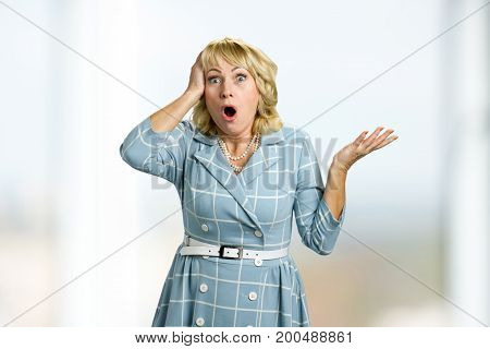 Surprised white-skin lady on white background. Mature blonde touching her head looking surprised with opened mouth and frowning eyebrows.