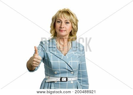 Elegant mature woman raised thumb up. Confident white-skin lady raised her thumb up on white background. Gesture everything is okay.