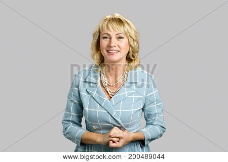 Attractive mature woman on grey background. Portrait of white-skin lady with smile isolated on grey background.