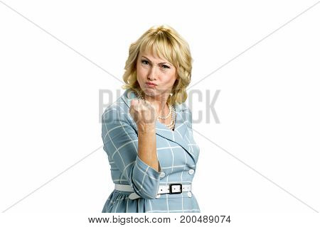 Angry mature woman making a fist. Frowning white-skin woman putting up fist over white background.