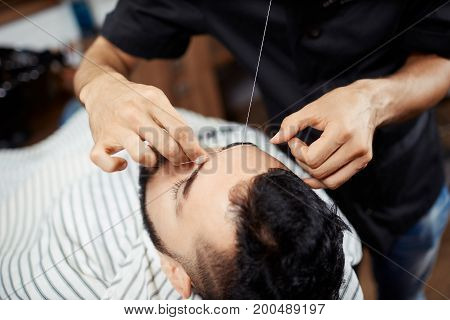Anonymous man doing eyebrow threading to young man lying in chair with eyes closed.