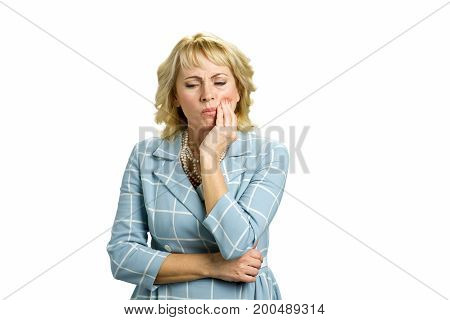 Mature woman having tooth pain. Confident middle aged woman suffering from terrible strong teeth pain, touching cheek standing on white background. Dentistry problem concept.