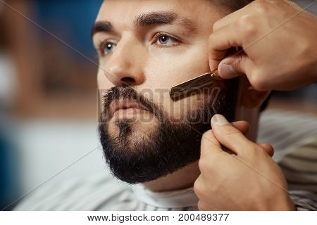 Anonymous barber shaving slightly beard of young man using sharp razor.
