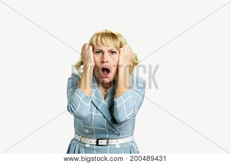 Horrified shocked mature woman. Portrait of stressed, frustrated shocked middle aged woman, pulling hair with open mouth on white background.