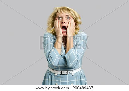 Portrait of shocked and stunned woman. Mature woman looking excited in full disbelief, open mouth and hands on face, grey background. Negative human face expression.