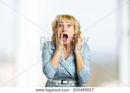 Surprise astonished middle aged woman. Close up portrait of white-skin woman looking surprised in full disbelief with open mouth and raised hands.