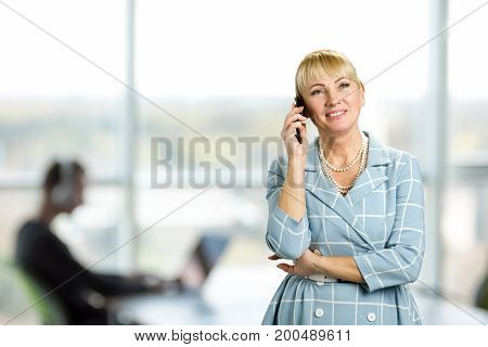 Happy mature woman talking on cell phone. Cheerful mature woman talking over phone on office window background. Happy mid woman using mobile phone.
