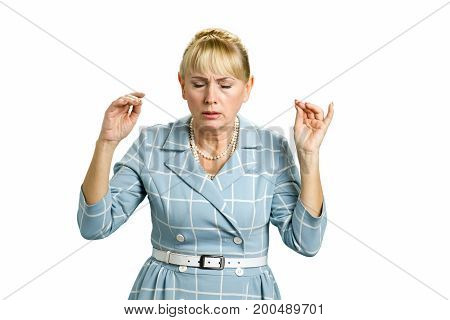 Focused mature woman maditating. Adult woman with closed eyes meditating on white background.