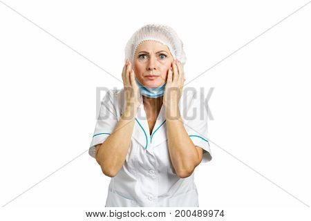 Surprised mature female doctor. Attractive female medical doctor in white suit looking shocked and scared.