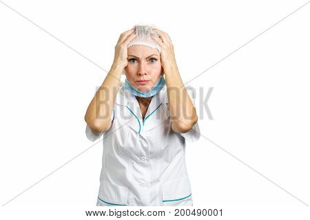 Female doctor shocked with hands on head. Close up portrait of a shocked female doctor or nurse wearing a mask and looking worried on white background.