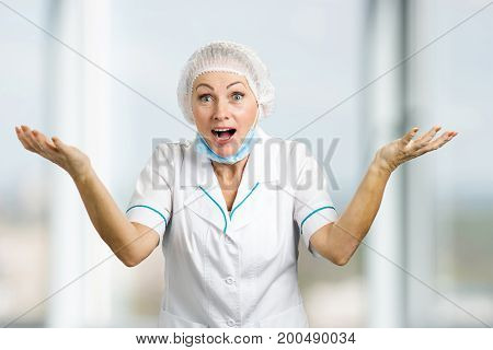 Happy female doctor gesturing with arms up. Cheerful mature nurse or doctor looking surprised on blurred background.