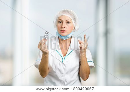 Female doctor with medical pills. Middle aged female doctor in white uniform giving medicine and pointing with index finger on blurred background.