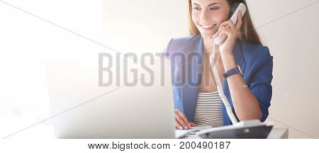 Portrait of a young woman on phone in front of a laptop computer.