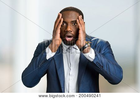 Shocked afro american businessman. Black man hold hands on head and open mouth with astonishment. Black man in full disbelief.