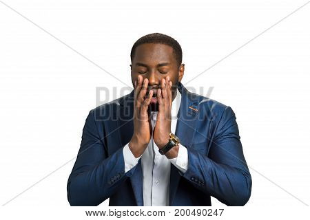 Shocked afro american on white background. Young black man with emotion of desperate. Darkskinned businessman closed eyes in despair.