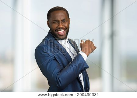 Cheerful businessman on blurred background. Confident smiling afro american manager, side photo. Enthusiastic business owner isolated.