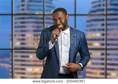 Man with microphone on urban background. Evening live perfomance. Afro american professional jazz singer.