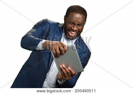 Expressive businessman play on computer tablet. Black executive emotionally use computer tablet. Dark skinned businessman impulsively operate on digital tablet.