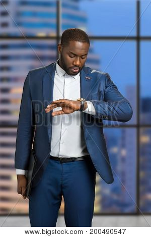 Businessman checking the time on his wrist watch. Young manager is looking on his watch on evening background. Expectation of late meeting.
