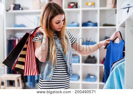 Young female shopaholic holding shopping bags and choosing ladies wear in clothing store.
