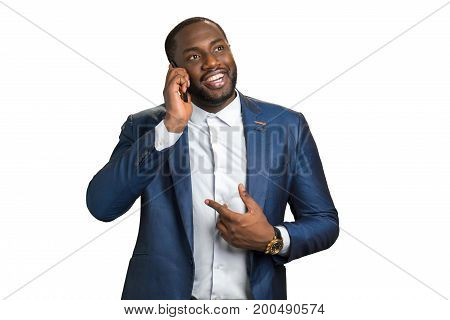 Happy businessman talking on mobile phone. Smiling black manager speaking on cellphone on white background.