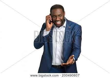 Succesful smiling businessman with mobile phone. Excited company director hearing positive news by cellphone. Happy black manager.