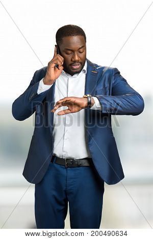 Businessman looking on watch with phone. Confident black executive speaking on mobile phone and looking on wrist watch.