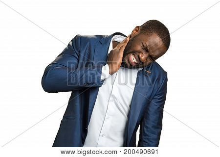 Stressed man with terrible neck pain. Black businessman feel neckache after hard day. Afro american businessman touching his neck and express painful feelings. Young man with neckache.