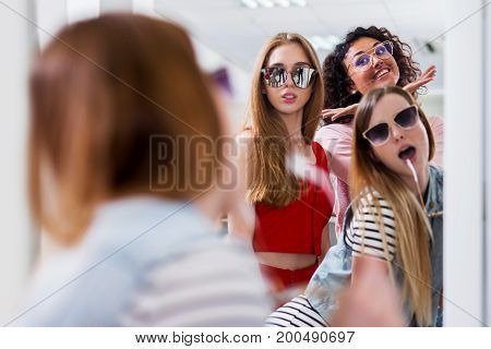 Trendy female friends trying on stylish sunglasses looking in mirror, smiling, having fun in accessory store.